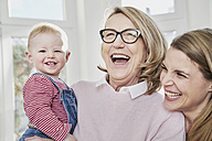 Happy grandmother, mother and baby girl at home - FMKF03591