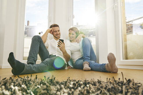 Smiling couple sitting on floor looking at cell phone - FMKF03603