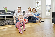 Happy familiy with baby girl in living room - FMKF03615
