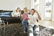 Parents with baby girl in living room - FMKF03621