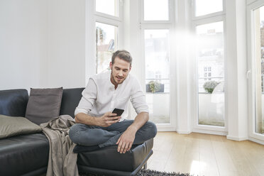 Man sitting on couch looking at cell phone - FMKF03624