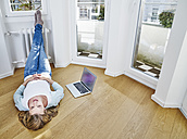 Woman at home lying on the floor next to laptop - FMKF03627