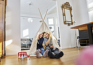 Smiling couple sitting on floor in a teepee - FMKF03636
