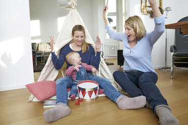 Happy grandmother, mother and baby girl playing at home - FMKF03648