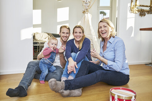 Happy familiy with baby girl in living room - FMKF03651