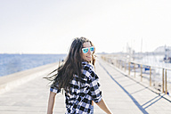 Young pretty woman wearing beach wear wlaking by the sea - GIOF02364