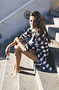 Young woan wearing shirt, sitting on stairs - GIOF02388