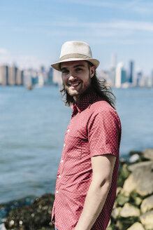USA, New York City, smiling man wearing hat at the waterfront with Manhattan skyline in background - GIOF02397