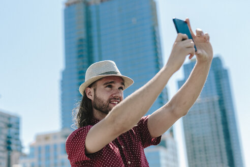 USA, New York City, man taking a selfie in front of skyscrapers - GIOF02400