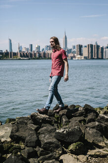 USA, New York City, man walking at the waterfront with Manhattan skyline in background - GIOF02403