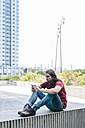 Man sitting on a wall with earbuds using cell phone - GIOF02406