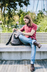 Man sitting on a bench with earbuds and backpack - GIOF02409