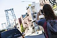 USA, New York City, man taking a picture of Williamsburg Bridge - GIOF02427