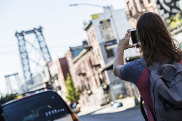 USA, New York City, man taking a picture of Williamsburg Bridge - GIOF02427