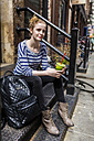USA, New York City, woman sitting on stoop drinking a smoothie in Manhattan - GIOF02441