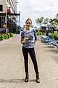 USA, New York City, portrait of confident woman with a smoothie in Manhattan - GIOF02450