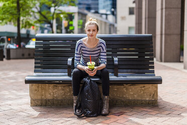 USA, New York City, portrait of woman sitting on a bench drinking a smoothie in Manhattan - GIOF02459