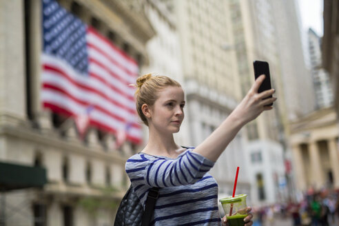 USA, New York City, woman taking selfie in front of New York Stock Exchange - GIOF02462