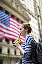 USA, New York City, woman drinking a smoothie in front of New York Stock Exchange - GIOF02465
