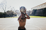 Barechested basketball player on court throwing ball - GIOF02472