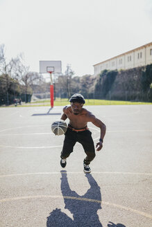 Barechested basketball player in action on court - GIOF02475
