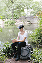 Young woman sitting at lakeside in park looking at cell phone - BOYF00735