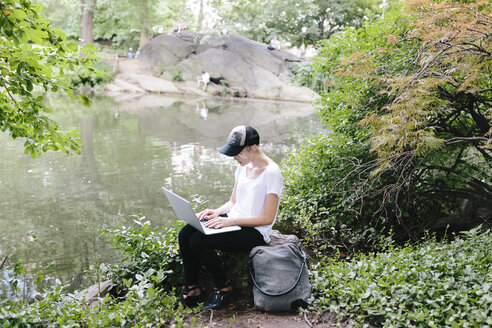 Young woman sitting at lakeside in park using laptop - BOYF00744