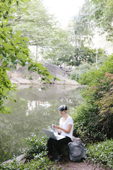 Young woman sitting at lakeside in park using cell phone and laptop - BOYF00747