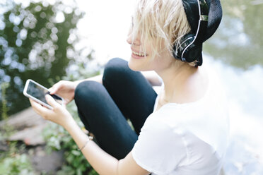 Young woman sitting at lakeside in park wearing headphones and holding cell phone - BOYF00750