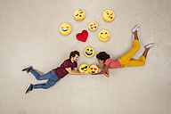 Happy couple, falling in love with emojies over their heads - BAEF01239