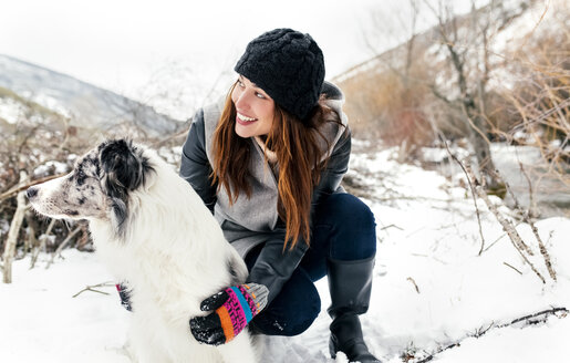 Young woman playing with her dog in the snow - MGOF03080