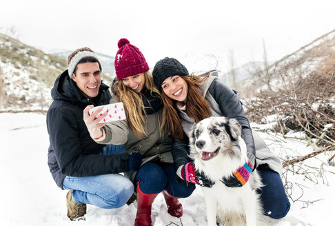 Three friends having fun taking a selfie with a dog in the snow - MGOF03086
