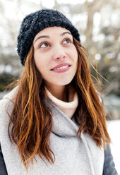 Young woman outdoors in winter looking up - MGOF03089