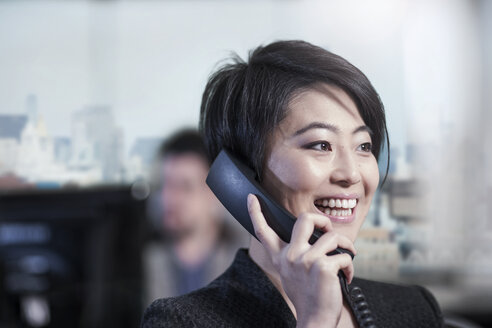 Smiling woman in office talking on phone - ZEF13164