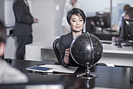 Woman looking at globe sitting at desk in city office - ZEF13194