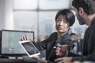 Woman showing tablet to colleauge in city office - ZEF13200
