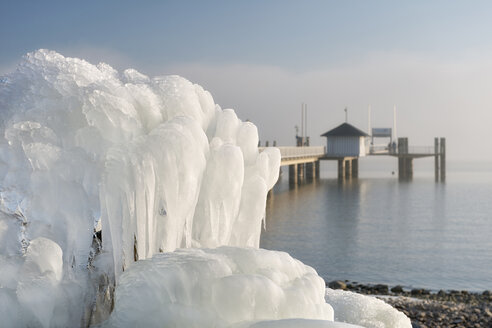 Germany, Immenstaad, icicles at fountain with jetty and Lake Constance in the background - SHF01952