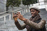 Smiling man taking selfie with smartphone - MAUF00988