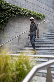 Young man walking down stairs - MAUF00997
