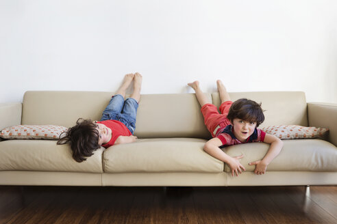 Twin brothers lying on the couch having fun - LITF00538