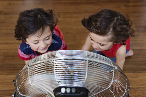 Twin brothers kneeling on the floor in front of fan having fun, top view - LITF00541