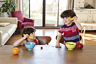 Twin brothers playing with bananas at the breakfast table - LITF00550