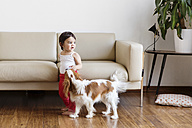 Toddler girl playing with dog in the living room - LITF00561