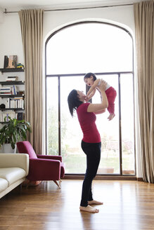 Mother playing with her baby girl in the living room - LITF00564