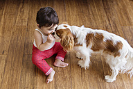 Toddler girl sitting on wooden floor sharing cookie with the dog - LITF00570