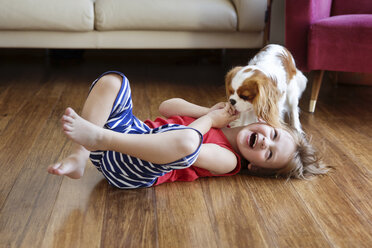 Little boy lying on the floor in the living room laughing because his dog licking his hand - LITF00573
