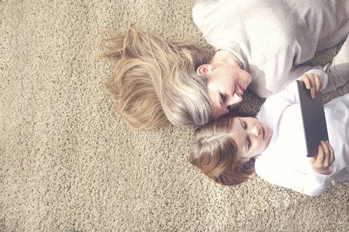 Mother and daughter lying on carpet looking at tablet - RTBF00751