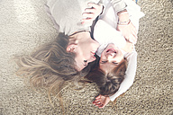 Mother and little daughter lying on carpet having fun - RTBF00754