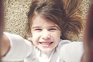 Portrait of grinning little girl lying on the carpet taking selfie - RTBF00757