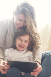 Mother and little daughter using tablet at home - RTBF00760